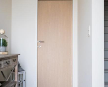 Een binnen deur in hout geeft een mooi contrast met de wit geschilderde binnen muren