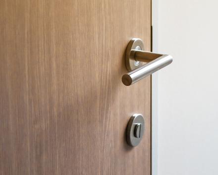 een degelijke binnendeur in hout met bijhorende deurklink in inox geplaatst door vakman Stefaan Desmet