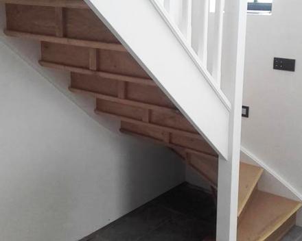 De combinatie van een houten trap met wit gelakte houten leuning is tijdloos en stijlvol