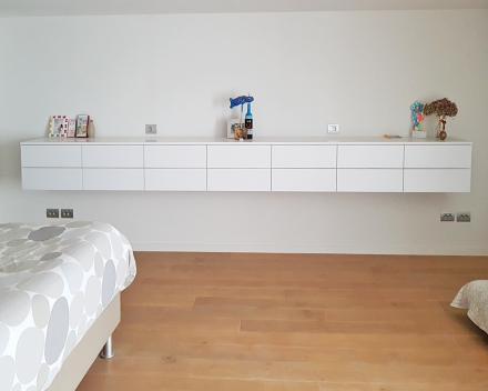 Een witte hangkast in de slaapkamer over de volledige breedte. Kwalitatief timmer- en maatwerk door Stefaan Desmet