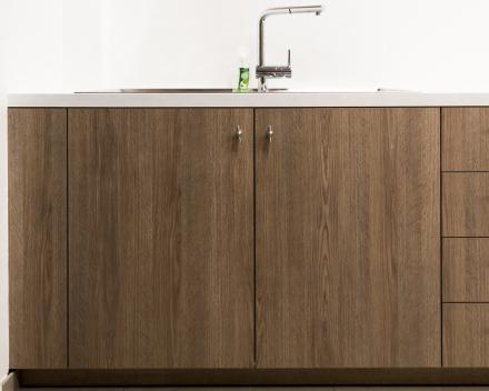 Een stijlvolle wasplaats met strakke houten opbergkasten